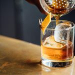 Cocktail d'un barman avec un zeste de citron