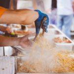personne servant des nouilles sautés dans un food truck